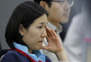 A foreign currency dealer of the Korea Exchange Bank reacts as she looks at a computer monitor at the bank's dealing room in Seoul