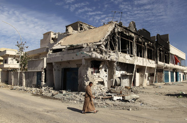 A man walks past a house which was destroyed during fighting between pro and anti-Gaddafi fighters in Sirt