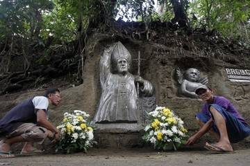 Filipino sculptors Val and brother Oca Suarez, arranges bouquet of flowers offered by visitors in front of image of blessed Pope John Paul II carved on hillside in Maragundon town