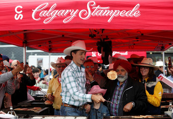 Prime Minister Trudeau flips a pancake at a Stampede breakfast during the Calgary Stampede in Calgary.