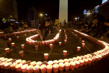 People light candles during Earth Hour in front of Buenos Aires' Obelisk