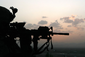 A U.S. soldier aims his weapon during an evening patrol in Arghandab valley