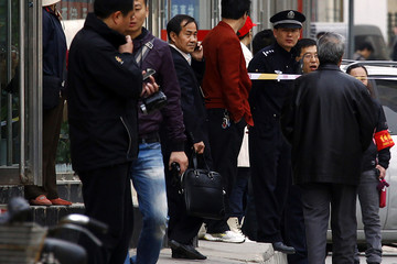 Chinese lawyer Cheng, who is representing disabled lawyer Ni and her husband Dong, is surrounded by policemen as he stands outside the courthouse in central Beijing