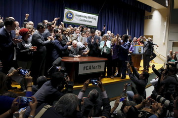 California Governor Jerry Brown signs a bill hiking California's minimum wage to $15 by 2023 in Los Angeles