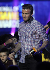 David Beckham holds his son Cruz's hand as he accepts the That's How I Roll award at the Cartoon Network's Hall of Game Awards in Santa Monica
