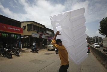 A man crosses a road while carrying a plastic water tank at a market in Mumbai