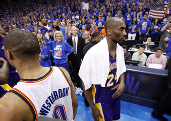 Lakers shooting guard Bryant walks past Thunder point guard Westbrook following Game 5 of the NBA western conference semi-finals in Oklahoma City