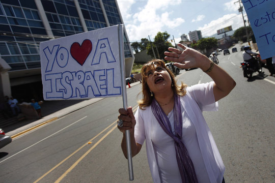 """A pro-Israel supporter prays while holding a poster that reads """"I love Israel"""" during a rally against Honduras' support for the Palestinian cause outside Presidential house in Tegucigalpa"""