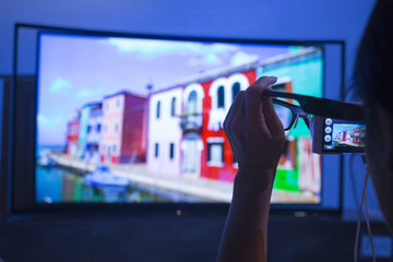 Woman takes photo of the multi-view 3D glasses for the Samsung Curved OLED TV during a news conference in New York