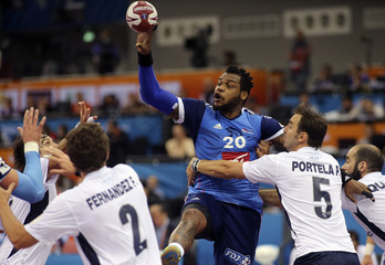 Sorhaindo of France passes past Fernandez and Portela of Argentina during their round of 16 match of the 24th men's handball World Championship in Doha