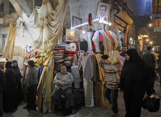 File photo of cloth vendor sitting at his stall as he waits for customers at the Al-Madina Souq market in Aleppo