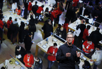 Apple CEO Tim Cook speaks with a projection of an Apple store behind him during an Apple event in San Francisco, California