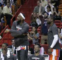 Miami Heats' LeBron James cheers as Dwyane Wade looks on late in the fourth quarter of their NBA basketball game against the New Jersey Nets in Miami