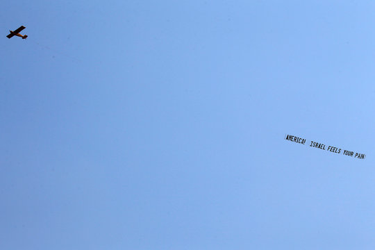 """An airplane pulls a banner that reads """"America! Israel feels your pain"""" as it flies the day after a mass shooting at the Pulse gay nightclub in Orlando"""