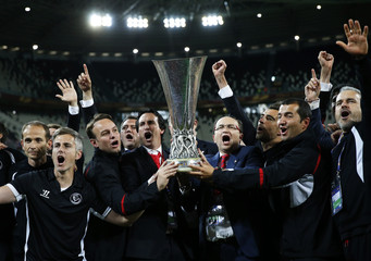 Sevilla's coach Unai Emeri holds the trophy after they beat Benfica on penalties in their Europa League final soccer match at the Juventus stadium in Turin