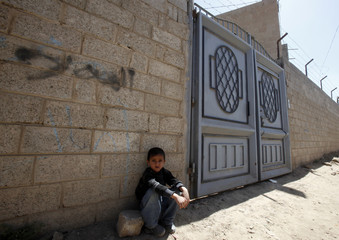 A boy sits outside house of woman believed to be involved in sending explosive packages bound for the United States, in Sanaa
