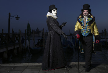 Revellers pose in front of St. Mark's Square during the Venice Carnival