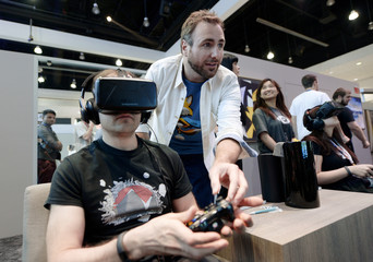 "Bettner, co-founder of Playful Corp which created new ""Lucky's Tale"" game for Oculus Rift, helps attendee try Oculus Rift Development Kit 2 headset at Electronic Entertainment Expo in Los Angeles"