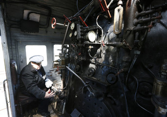 Kireyev, an 83-year-old veteran who worked on steam locomotives for the most of his life, sits inside a cabin of an old steam locomotive at a regional reserve base for the Trans-Siberian railway near the village of Vagino