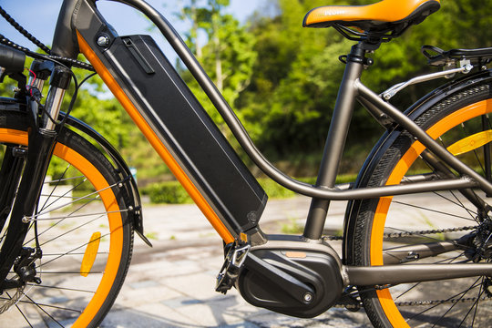 Orange and black electric bicycle / ebike close up, background trees