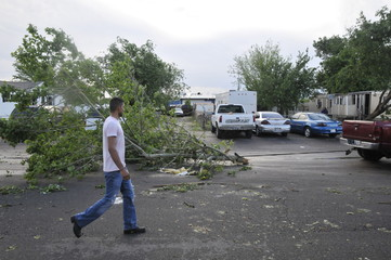 A resident of a mobile home park watches as his friend tows away a fallen tree limb in Oklahoma City
