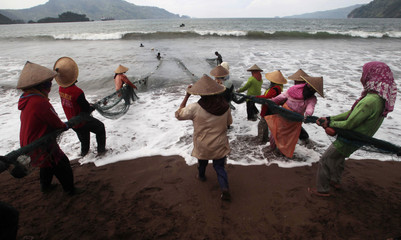 Fishermen tow nets in bad weather in Trenggalek coast in East Java province