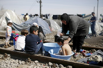A woman bathes a child at railway tracks at a makeshift camp for migrants and refugees at the Greek-Macedonian border near the village of Idomeni