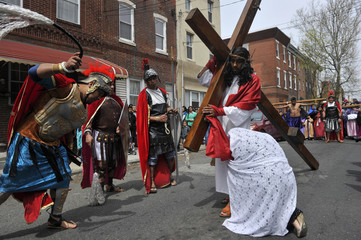 A man dressed as Roman soldier whips Jose Miguel Almaraz, dressed as Jesus Christ, during 'Way of the Cross' procession through streets of Philadelphia during Good Friday