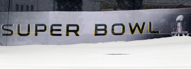 A snow bank obscures the logo for Super Bowl XLV outside Cowboy Stadium in Arlington