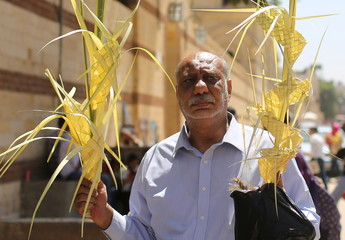 An Egyptian Coptic Christian man carries palm decorations during Palm Sunday as he waits outside a Church in Old Cairo