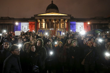 People take part in a vigil to pay tribute to the victims of the Paris attacks, at Trafalgar Square in London