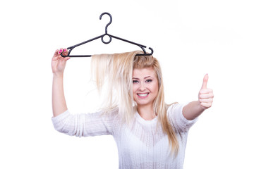 Blonde woman with hair in clothes hanger