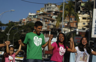 Youths sing before the arrival of the World Youth Day symbols at the Vidigal slum in Rio de Janeiro