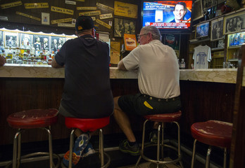 Picture of U.S. Republican presidential candidate Scott Walker is seen on a television above bar patrons at the Billy Goat Tavern in Chicago, Illinois
