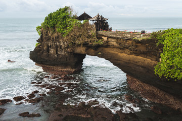 Garden Poster Temple Sacred Balinese temple Tanah Lot. Pura Batu Bolong on the edge of a cliff at coastline with hole in the rock. Traditional style and architecture of Bali. Holy place for local indonesian people