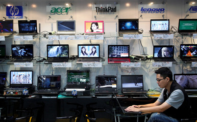 A shop attendant sits in front of a wall of laptops at a computer mall in Taipei