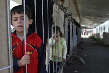 A Syrian refugee boy waits at the UNHCR as they receive aid in Tripoli