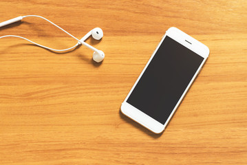 Top view image of smartphone with earphone on wooden table