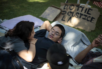 Iman Issa and Victor Valdez rest at the Occupy LA protest camp in Los Angeles