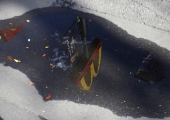 The McDonald's sign is reflected in a puddle in Tokyo