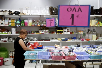A woman looks at goods displayed for sale inside a one-Euro shop in Athens