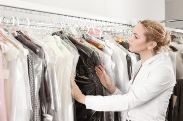 Female laundry worker with clean clothes on rack at dry-cleaning