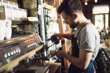 Young male barista preparing drink at coffee machine