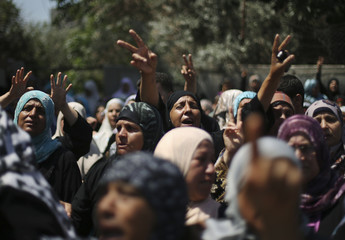 Palestinian relatives mourn during the funeral of members of Hamad family in the town of Beit Hanoun in the northern Gaza Strip