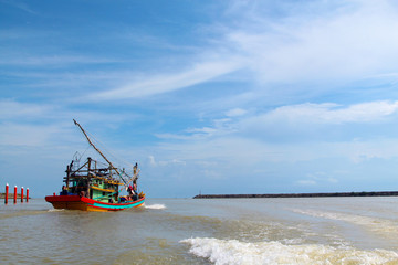 A seascape view of a fisherman fishing boat heading towards an open ocean for fishing over a blue bright sky and a cloudy day. Image shoot from a boat at Kuala Besut Jetty, Terangganu, Malaysia