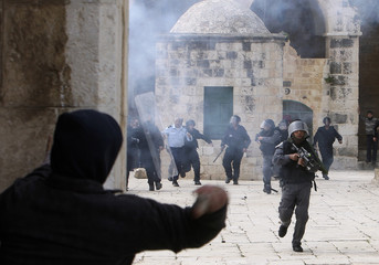 A Palestinian throws a stone at Israeli border police during clashes in Jerusalem's Old City
