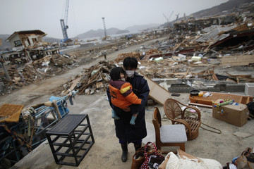 Ichiro Okazawa holds his daughter Hiori in the ruins of their home as they returned to retrieve belongings in the destroyed residential part of Ofunato