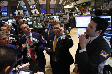 Traders gather at the post that sells Northrop Grumman on the floor of the New York Stock Exchange