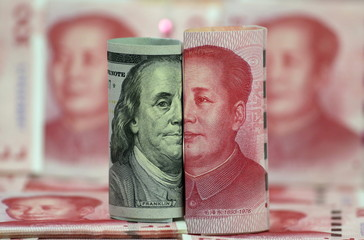 A Benjamin Franklin U.S. 100-dollar banknote and a Chinese 100-yuan banknote depicting the late Chinese Chairman Mao Zedong, are seen in a picture illustration in Beijing