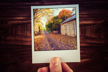 Male hand holding polaroid photo of rural road passing wooden shed among yellow and orange trees in Autumn Australia. Travel memories scrapbooking